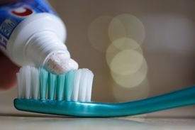 Close up of placing toothpaste on toothbrush.