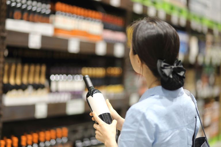 Woman holding a bottle of wine in wine store