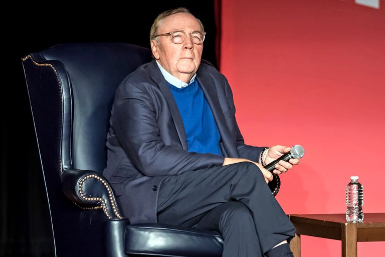 James Patterson sits in a blue leather chair onstage in Philadelphia to discuss his book,