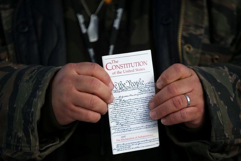 Man holding a small copy of the US Constitution