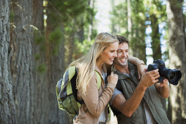 Couple looking at digital camera in woods
