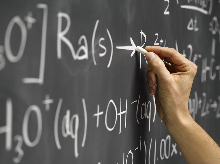 Person writing out a chemical equation on a blackboard
