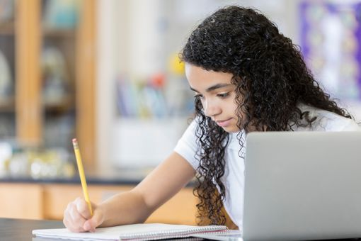 Middle school student completes homework at school