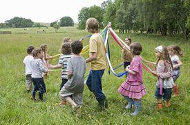 kids doing a maypole dance in a field