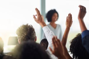 people raising hands to ask questions of a speaker