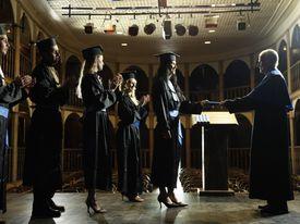 Dean handing out diploma, graduates applauding