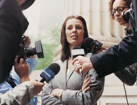 A woman being interviewed and photographed