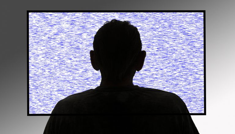 Person in front of flickering tv screen