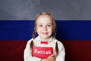 Learn russian language. Child girl student with book against the russian flag background