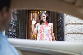 Woman waving to man leaving in car