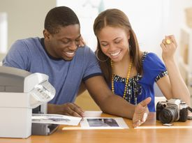 Young couple smiling while printing out photographs