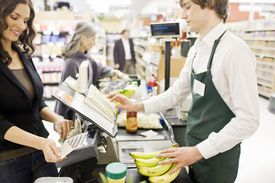 Muchacha latina pagando compra en supermercado.