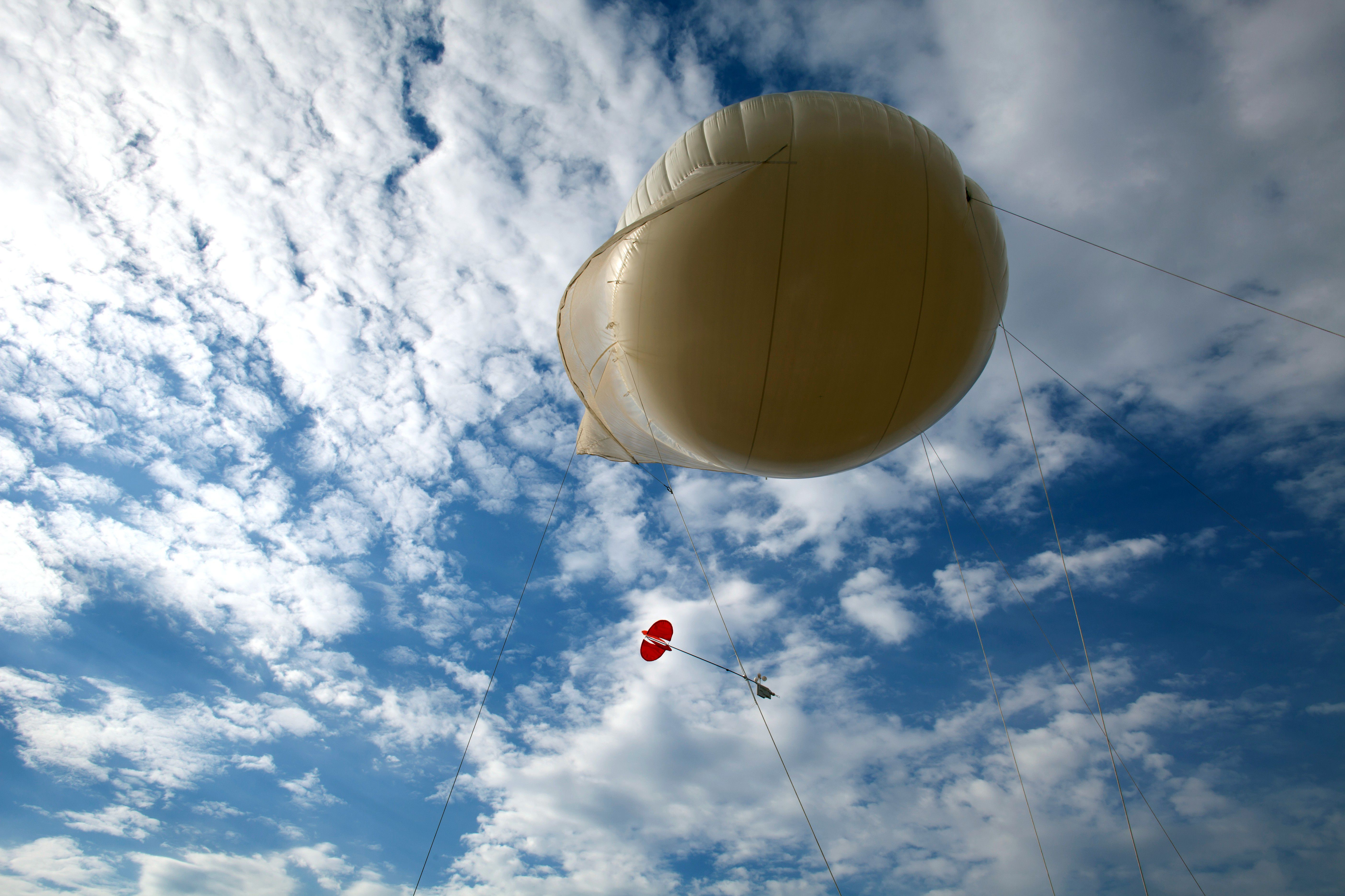 A tethered weather balloon for testing national air quality slowly rises into the sky
