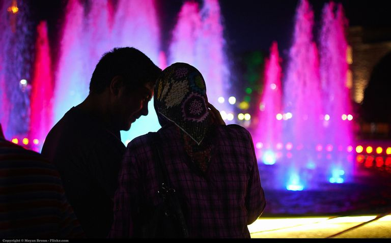 Turkey, a typical muslim couple in front of the fountain of the main square of Istanbul