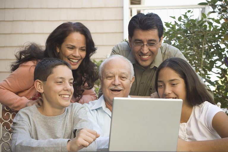 Family gathered around laptop computer