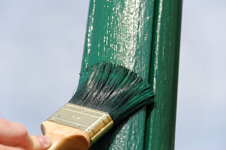 close-up of paint brush applying deep green-grey paint