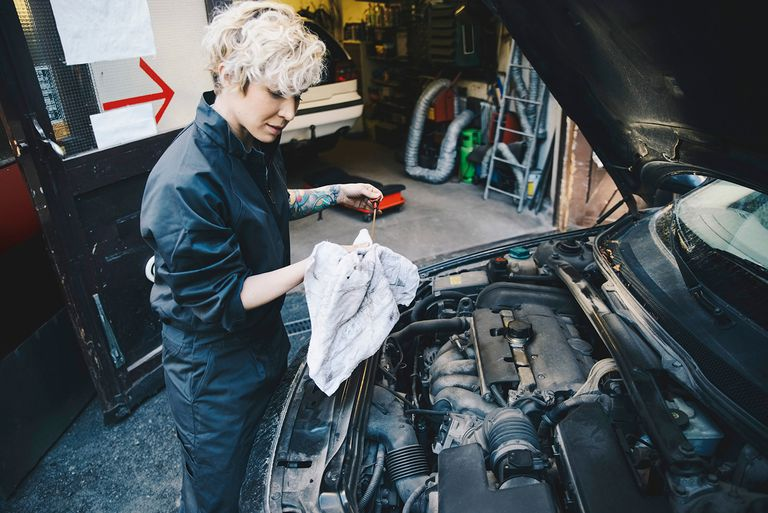Side view of female mechanic checking oil with dipstick outside auto repair shop.