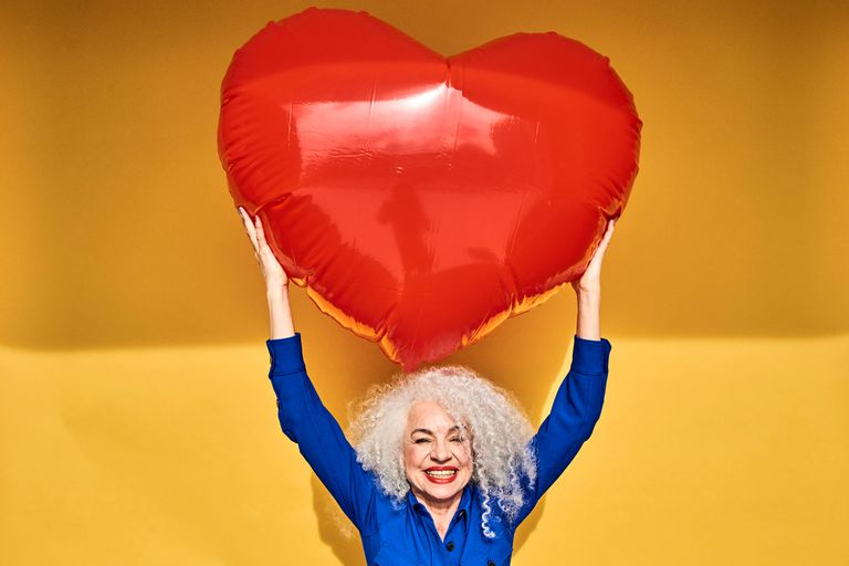 Woman holding inflatable heart over her head