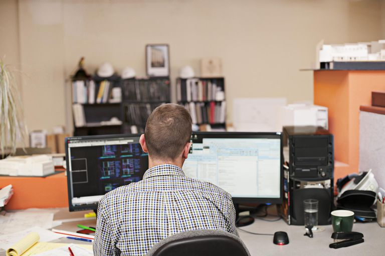 Man working at computer with multiple monitors.
