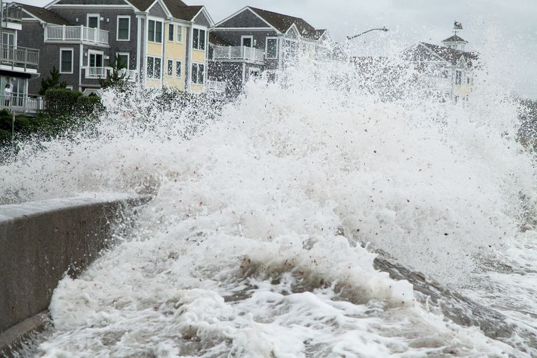 Hurricane storm surge hitting homes on a beach.