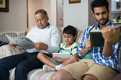 Boy with grandfather and father sitting on sofa
