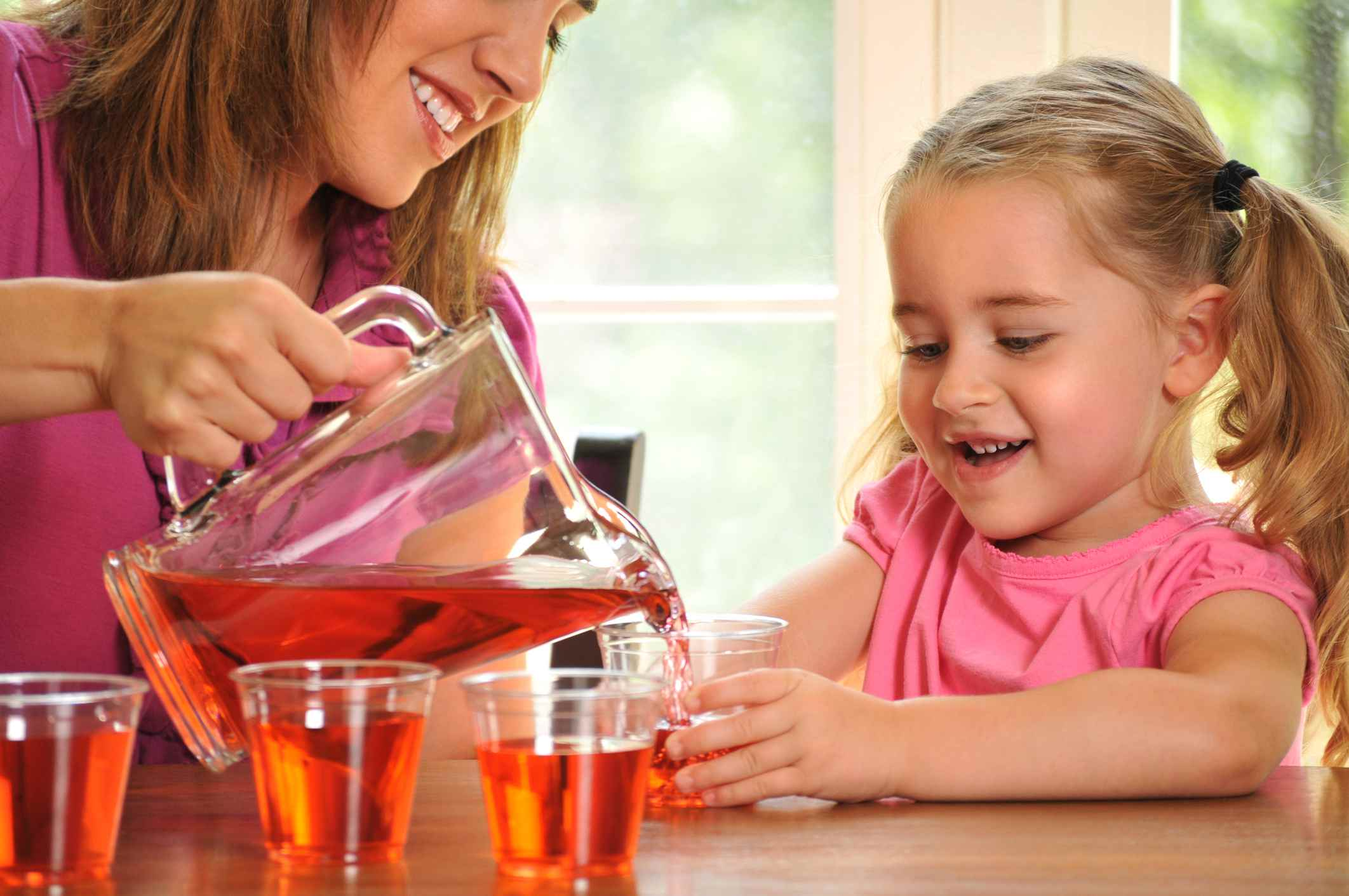 Young Girl Helping her Mother Pour Juice for her Friends