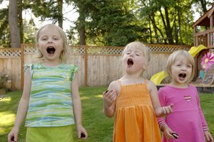 Three girls (3-5) eating cookies in yard, mouths open, portrait