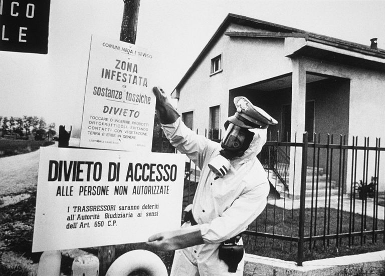 A state policeman pins up warning signs around the town of Seveso in Italy, following the area's contamination by a toxic cloud.
