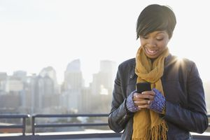 Smiling woman text messaging on patio