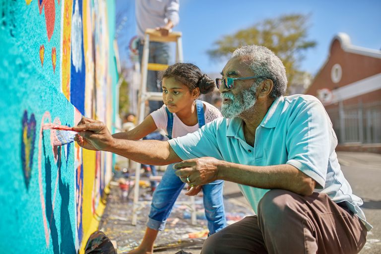 grandfather and granddaughter painting mural