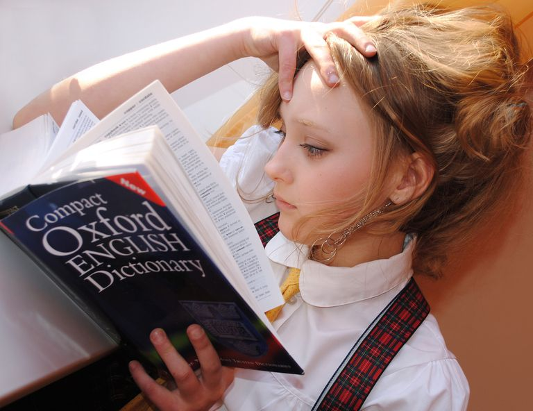Young girl looking at an English dictionary.