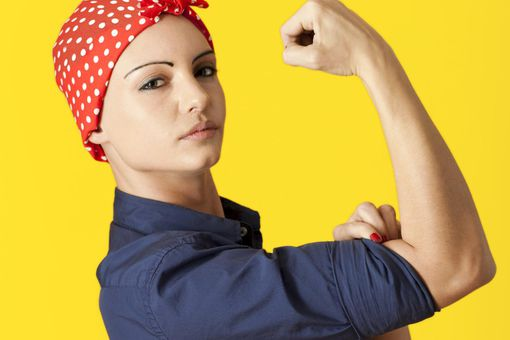 Strong Caucasian woman wearing blue shirt and red polka-dot bandana like 'We Can Do It' painting's Rosie the Riveter