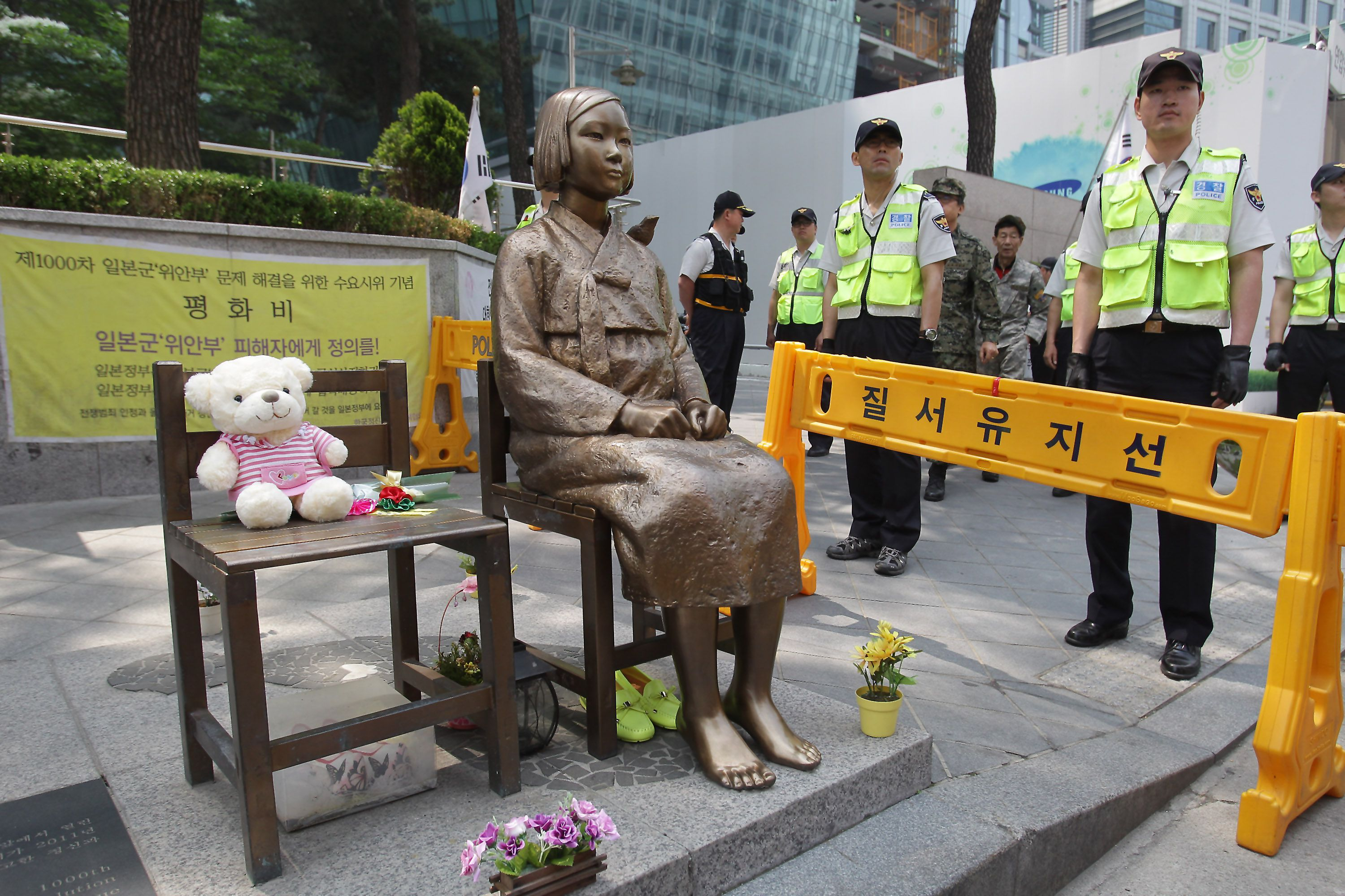 Guards standing around comfort woman statue in Seoul, South Korean.