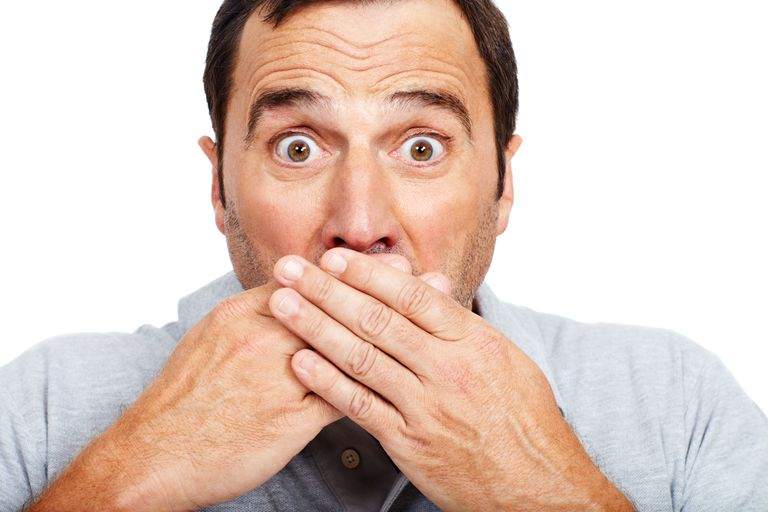 Man covers his mouth while making a shocked expression.