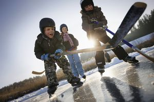 Young children playing hockey on a frozen pond.