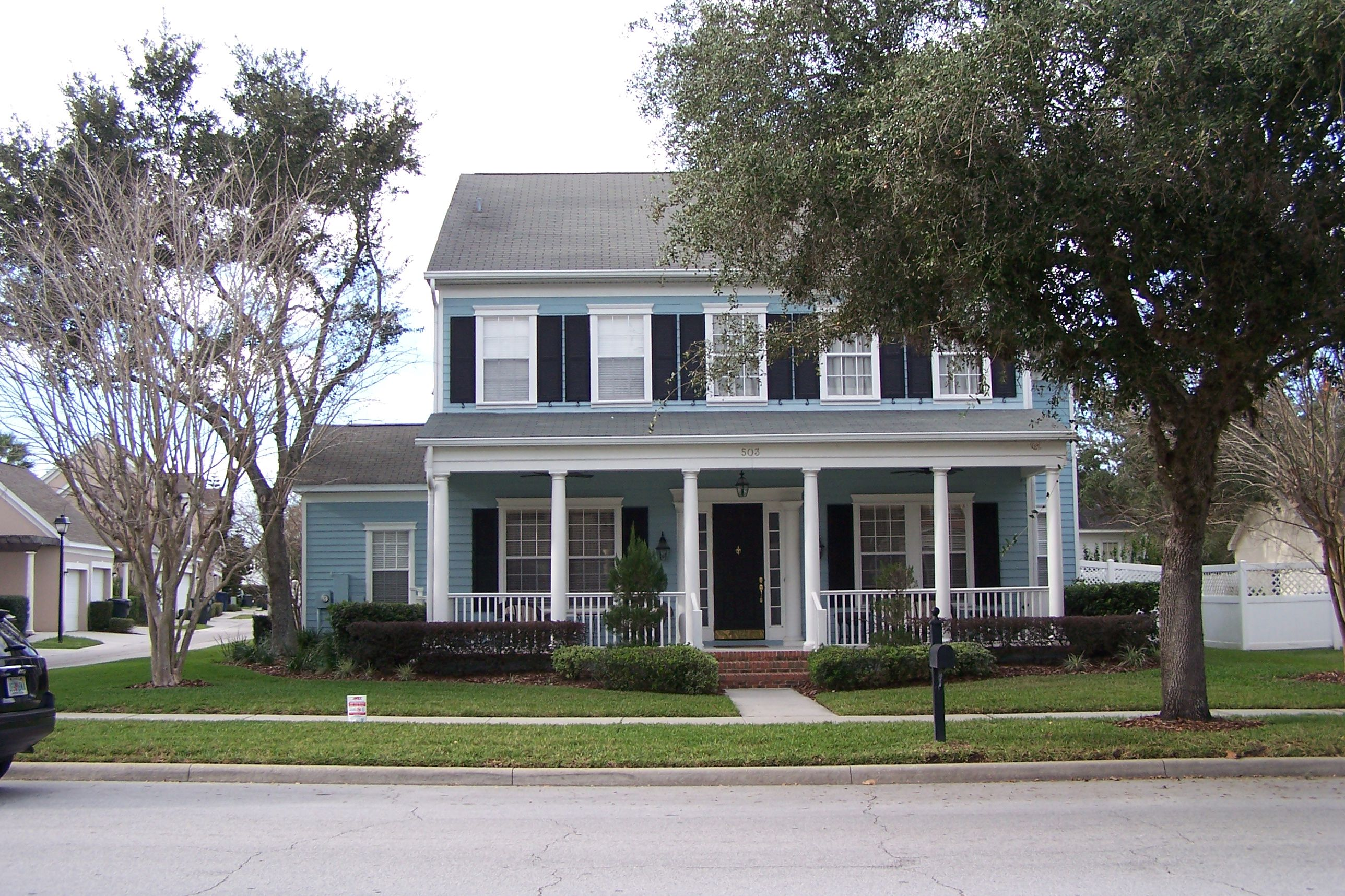 Blue-Sided Farmhouse with Shutters and full-sized porch along the front