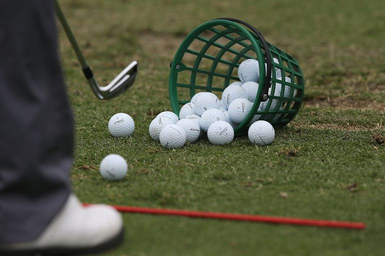 Bucket of golf balls and golf practicing