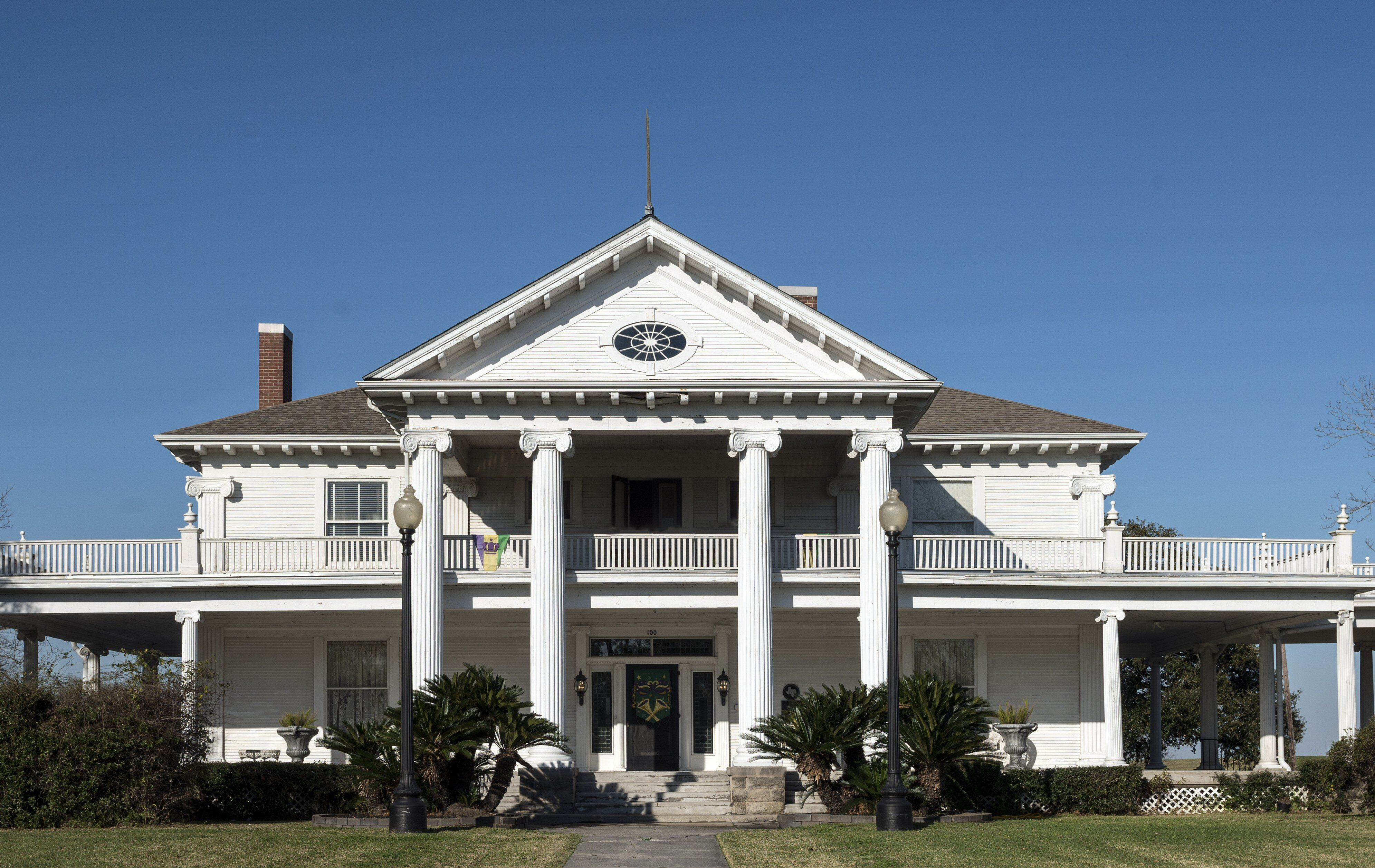 wide two story house with large portico, columns, and second floor wrap around porch