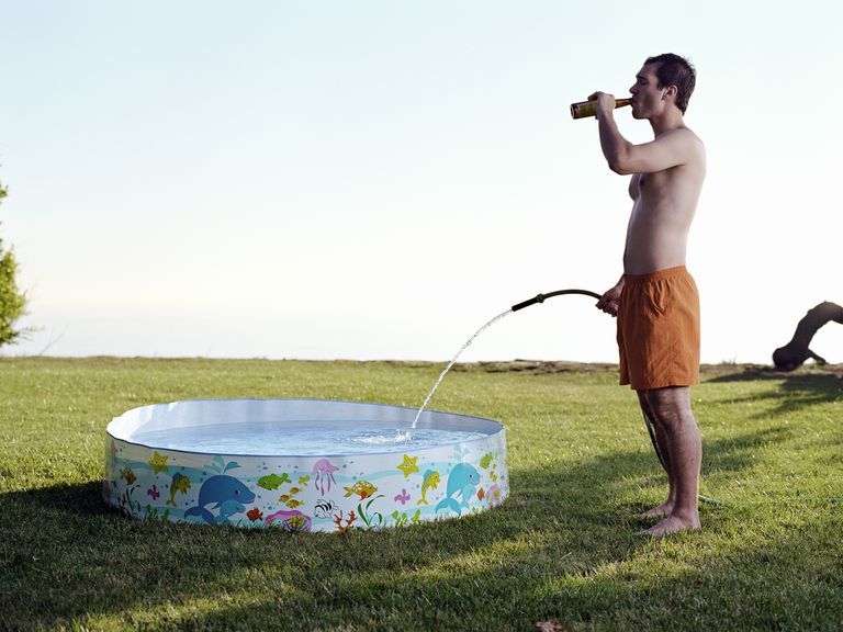 man drinking beer and holding hose filling a kiddie pool