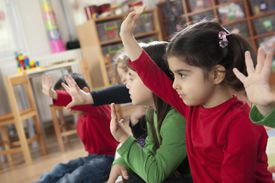 Young students raising their hands in a classroom.