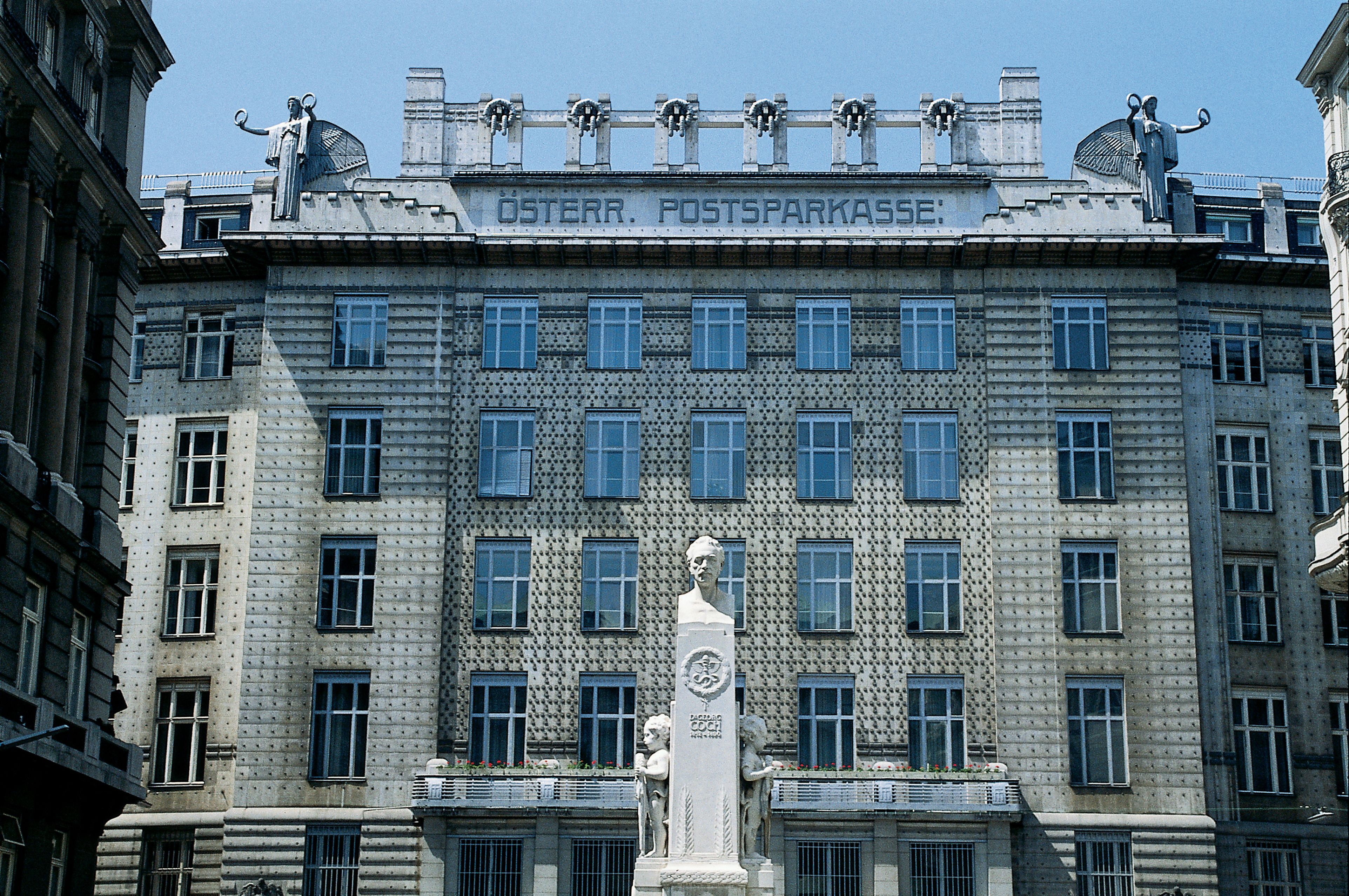 ornate facade of multi-story building emblazoned with roof sculpting and labeled OSTERR POSTSPARKASSE