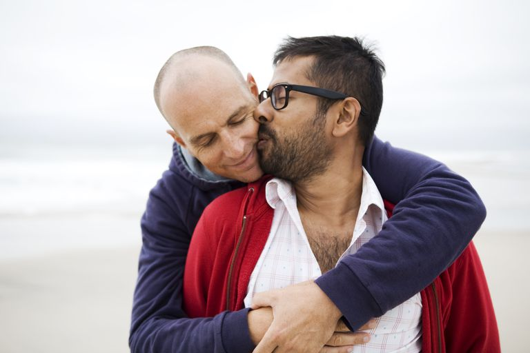 two men kissing on beach