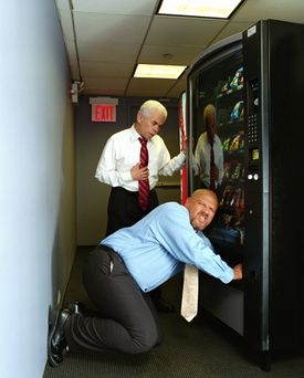 One man on his knees reaching up into a vending machine and other man watching him