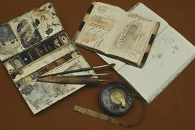 open watercolor box, brushes, tape measure, and open notebooks
