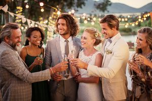 Young couple and their guests with champagne flutes