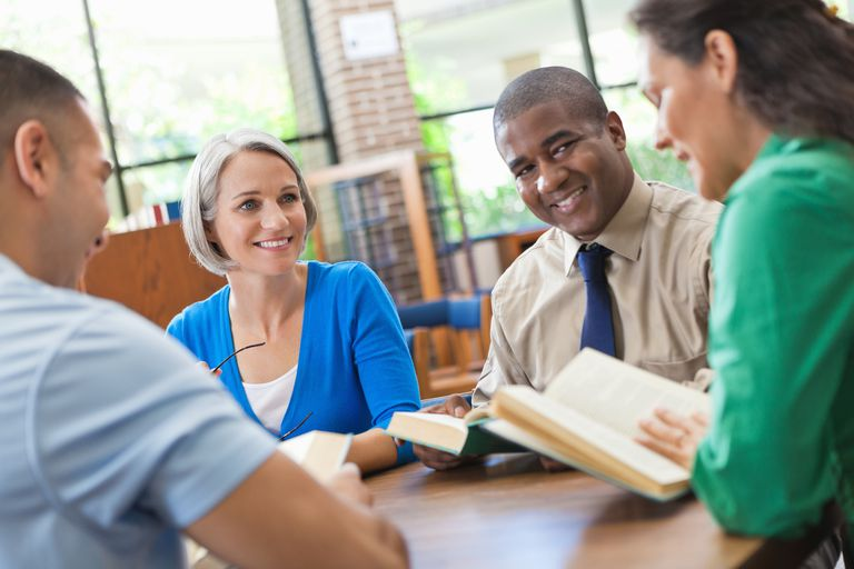 Group of adults happily discussing a book in library