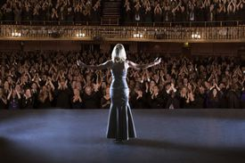 Performer standing with arms outstretched on stage in theater