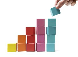 hand stacking blocks in ascending piles