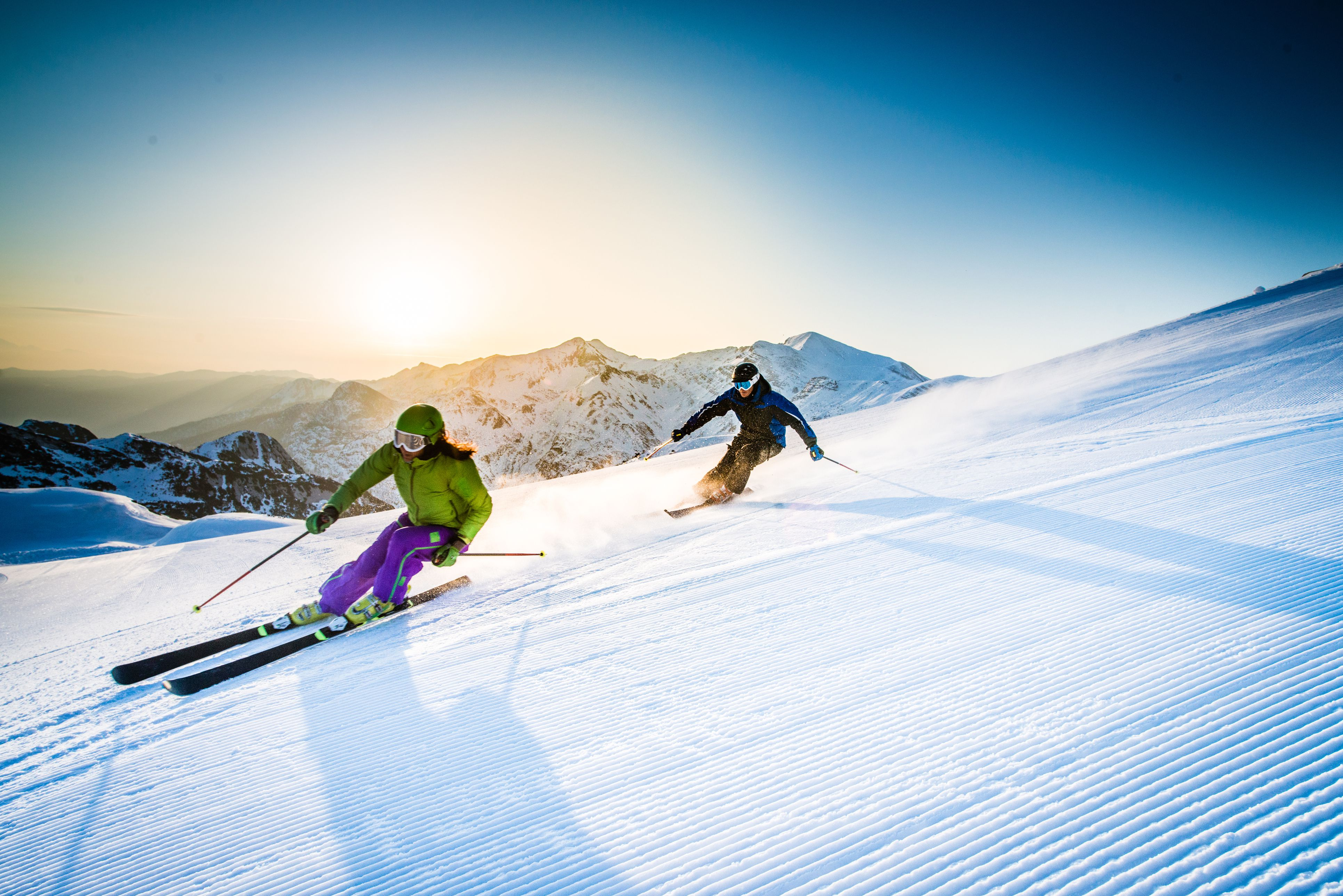 Man and woman skiing downhill