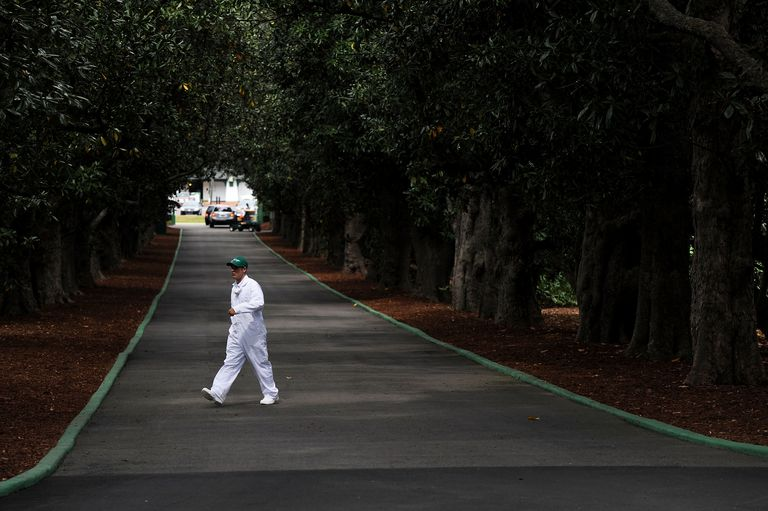Caddie walking across Magnolia Lane that leads to Augusta National Golf Club